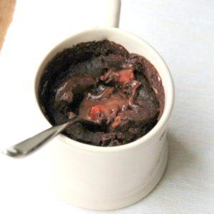 A decadent vegan dessert! Chocolate mug cake with a melting chocolate hazelnut and strawberry center. So easy and so yummy!