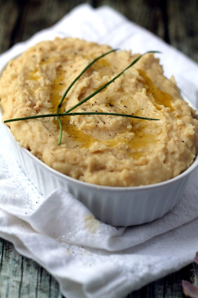 A great healthy alternative to mashed potatoes, you won't believe how creamy and comforting white bean mash can be. This recipe is packed with roasted garlic and cheddar cheese for maximum flavor.
