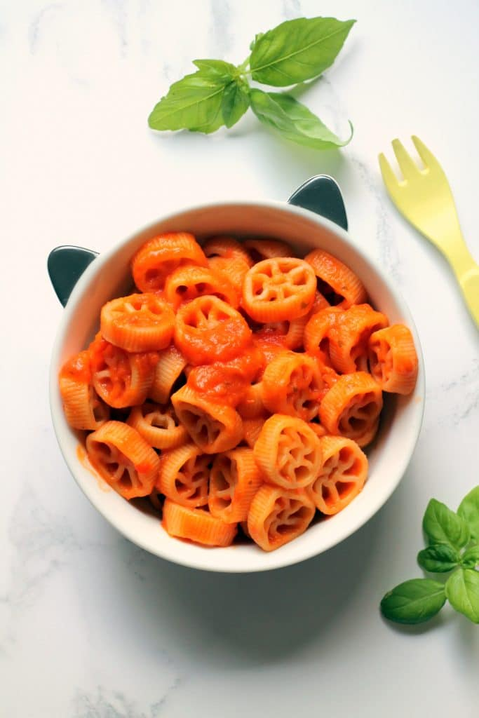 A top down view of a pasta sauce for babies served with wheel pasta shapes in a small bowl