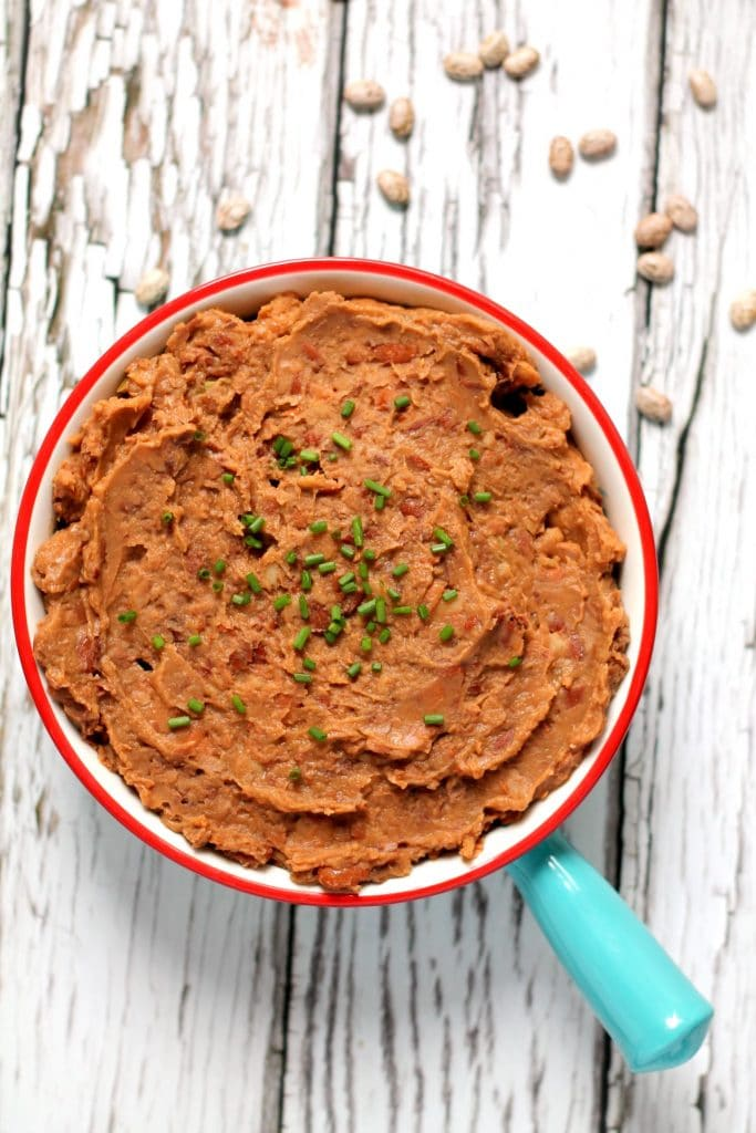These flavor packed vegan refried beans are made in the slow cooker and have a delicious smoky edge to them! Cooking dried pinto beans in the slow cooker is an economical way to fill your freezer with tasty refried beans for quick and easy weeknight meals.