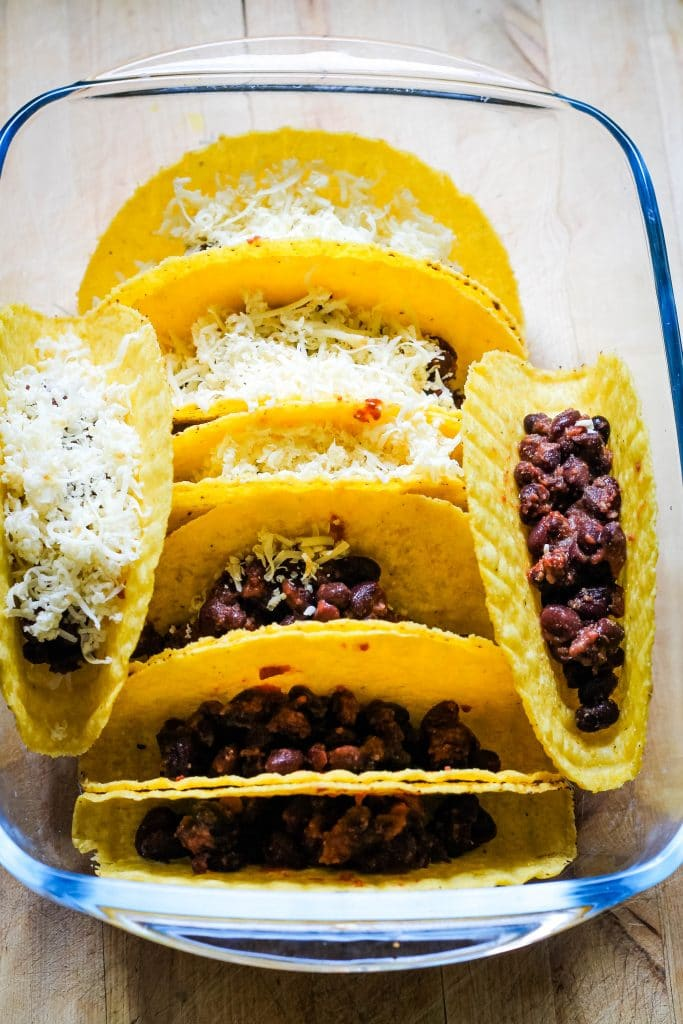 An image showing how to make baked tacos - taco shells are inside a dish, with beans and cheese stuffed inside.