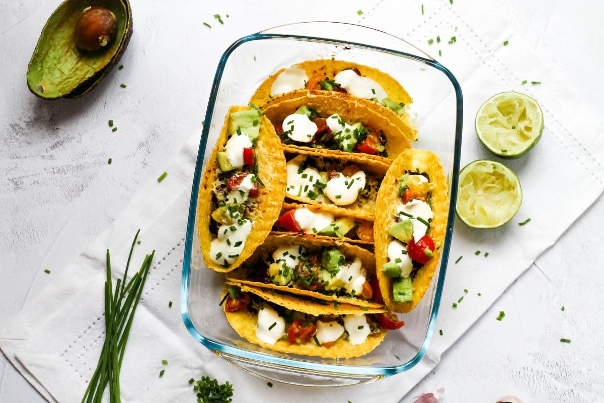 Landscape view of a tray of oven baked tacos with beans and cheese and a variety of topping, with herbs, limes and avocado skins to the side
