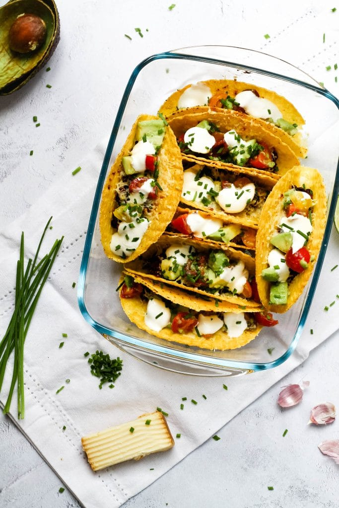 A top down image of baked tacos with avocado and herbs scattered around