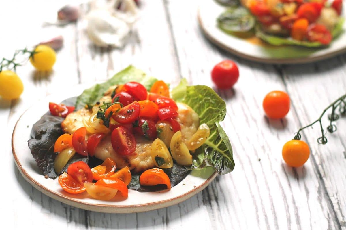 Oven baked halloumi topped with cherry tomato bruschetta topping - atop a bed of lettuce leaves.