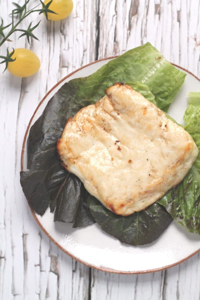 A slab of balsamic baked halloumi on a bed of lettuce leaves