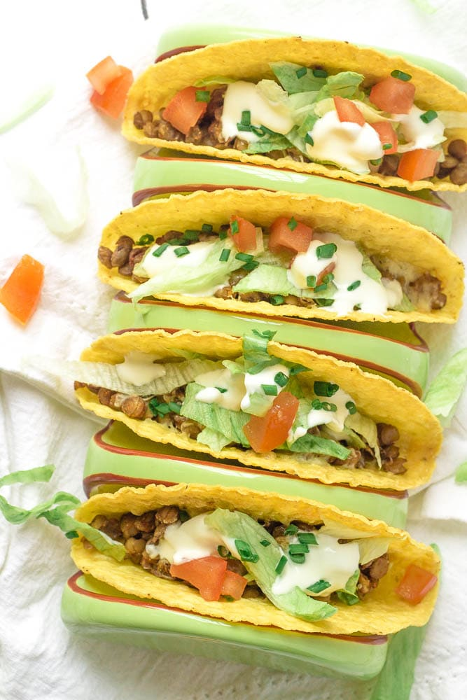 Four lentil tacos with toppings.