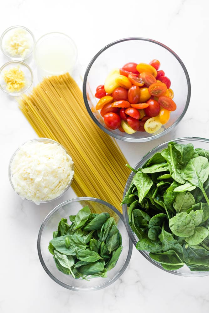 Bowls of prepped ingredients: spinach, basil, cheese, tomatoes, lemon juice and zest, dried spaghetti