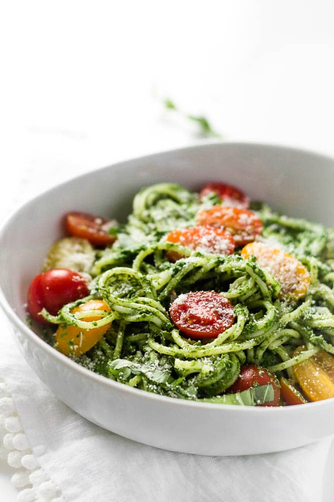 A bowlful of spinach spaghetti with cherry tomatoes, from the side on.