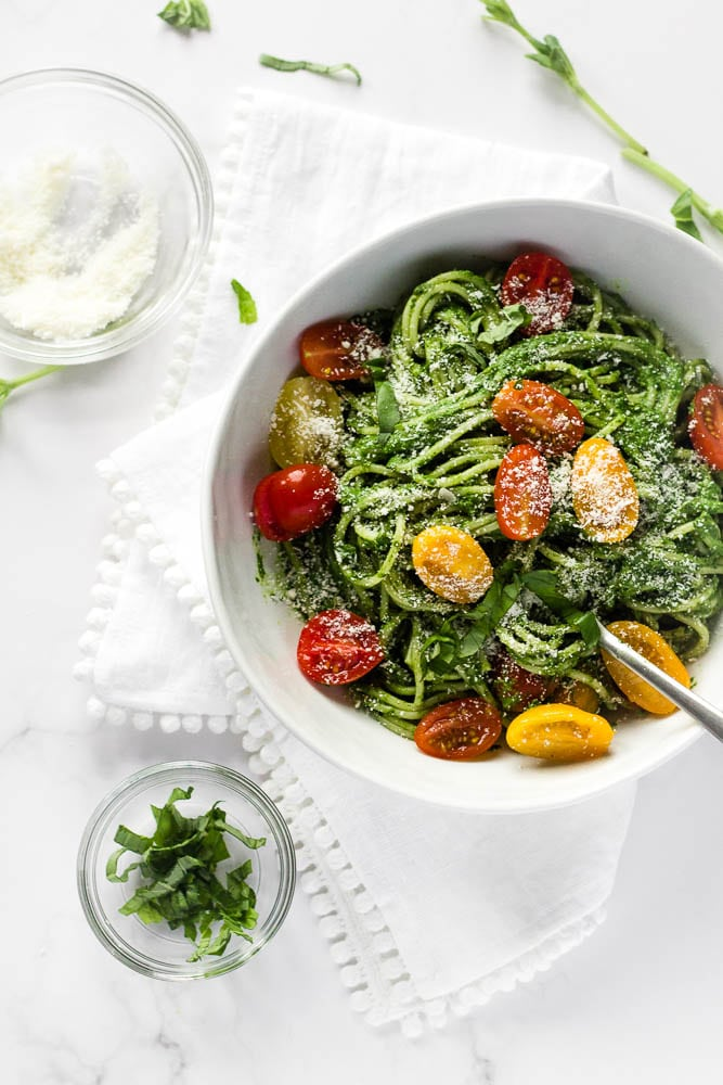 A bowl of spinach spaghetti sauce with cherry tomatoes.